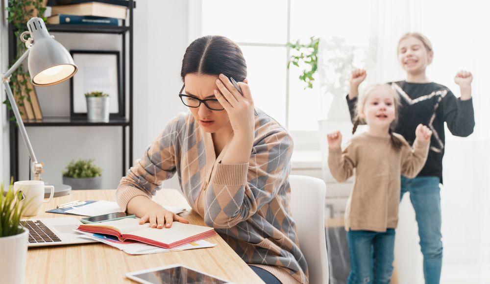Frau arbeitet im Wohnzimmer an ihrem Laptop. Sieht gestresst aus. Im Hintergrund spielende Kinder